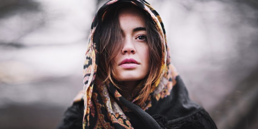 Kobieta owinięta w szalik, a tle rozmyty jesienny krajobraz.