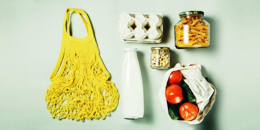 Jedzenie wyłożone na stole (makaron w kształcie torby na zakupy, szklana butelka mleka, wytłaczanka jajek, dwa słoiki i siatka pomidorów)