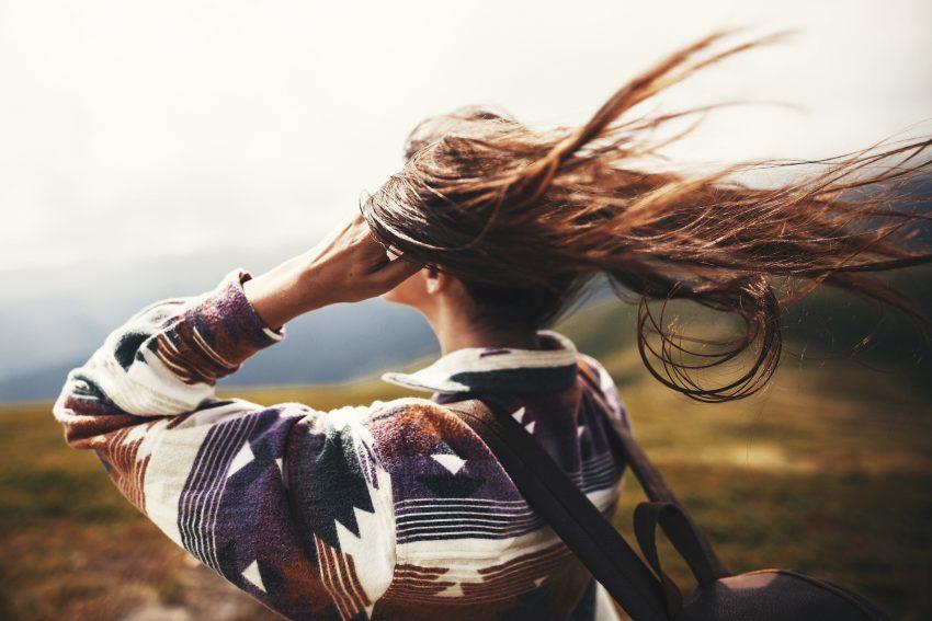 Kobieta stoi tyłem. Wiatr rozwiewa jej włosy