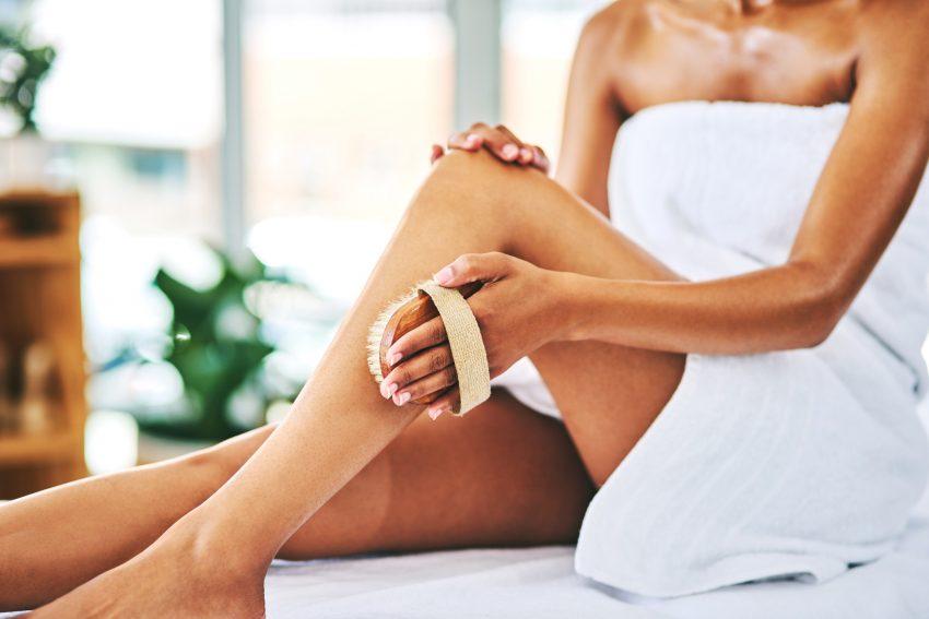 Kobieta siedzi w ręczniku i szczotkuje szczotką łydkę