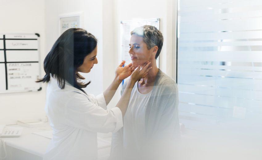 Lekarka bada gardło pacjentce, dotykając szyi w gabinecie lekarskim. Panie widać przez szybę