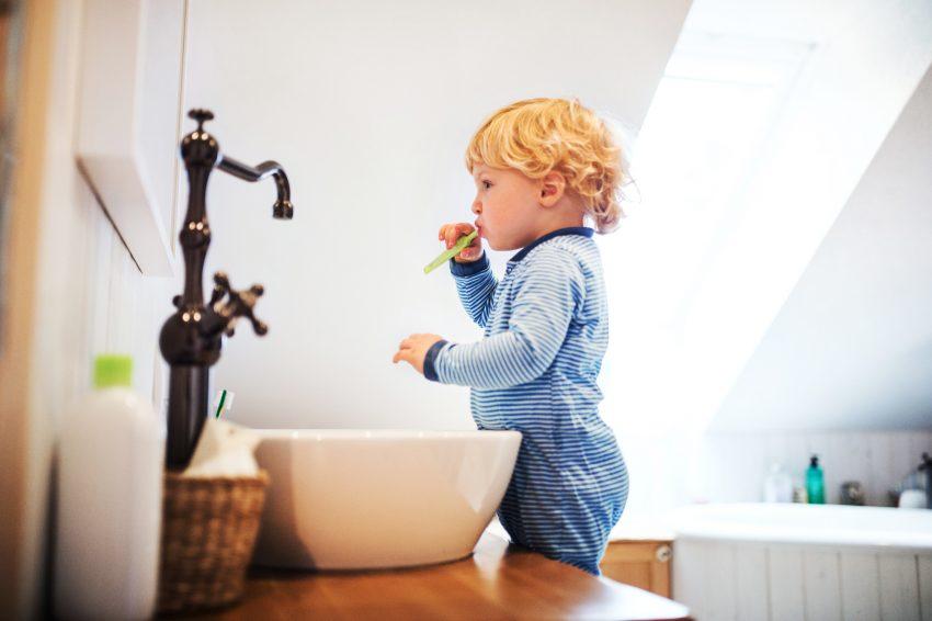 Mały chłopiec stoi na krzesełku przy umywalce, patrzy w lustro i myje zęby