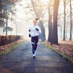 Kobieta biegnie ulicą w parku. Jest ubrana w sportowe ciuchy. Dookoła są liście, widać, że jest jesień
