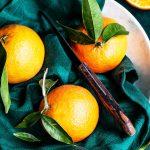 Trzy pomarańcze i nóż leżą na talerzy pokrytym ścierką