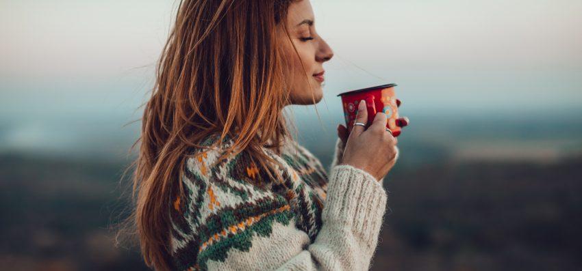 Kobieta stoi na dworze w grubym swetrze. W rękach trzyma kubek
