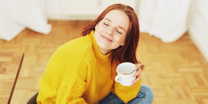 Uśmiechnięta kobieta z kubkiem herbaty