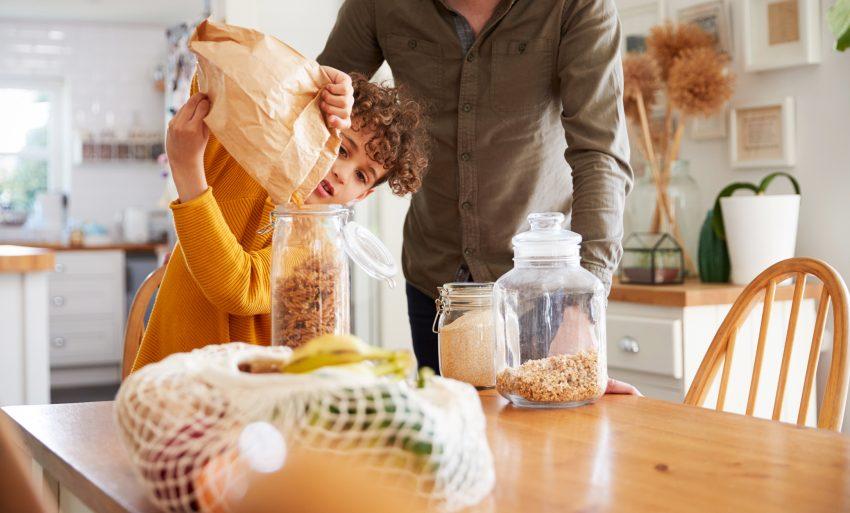 Dziecko przesypuje płatki śniadaniowe z torebki do słoika. Na stole leżą zakupy i słoiki.