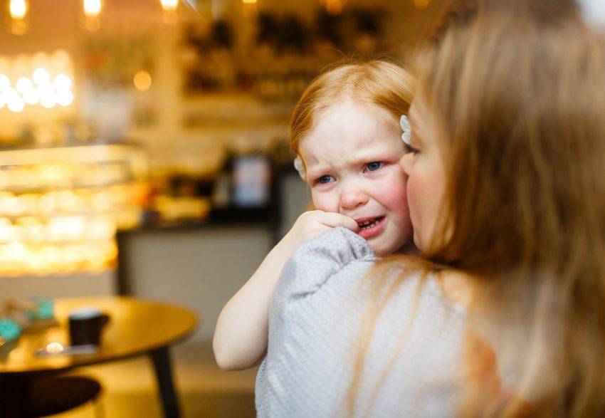 Płacząca dziewczyna na rękach mamy