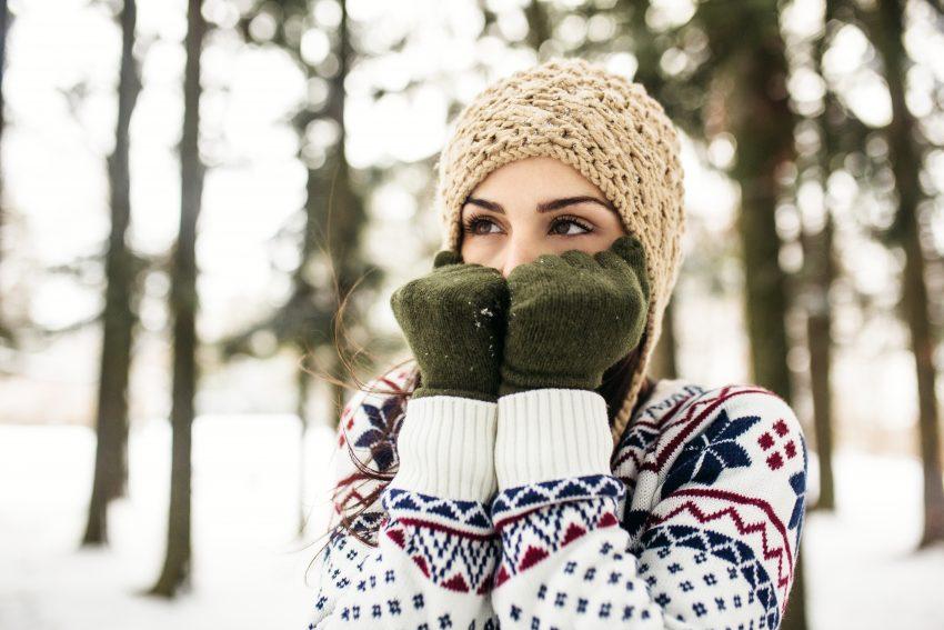 Kobieta stoi w lesie, jest zima i śnieg. Ubrana jest w sweter, czapkę i rękawiczki. Ręce trzyma przy tywarzy, patrzy się w bok