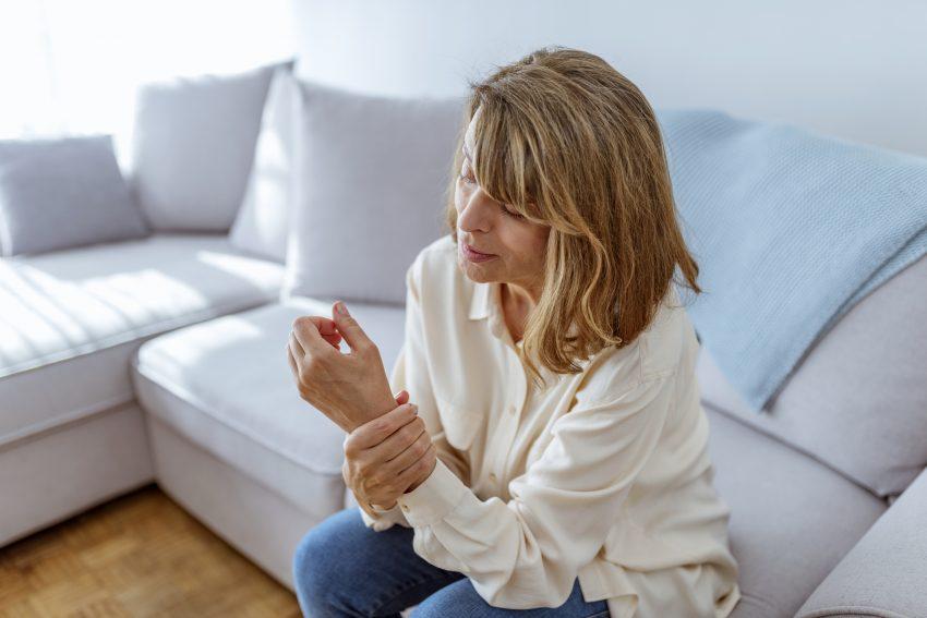 kobieta trzyma się za zdrętwiałą rękę, siedząc na kanapie