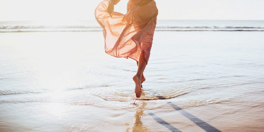 Kobieta biegnie po plaży przy linii morza. ma zwiewną sukienkę