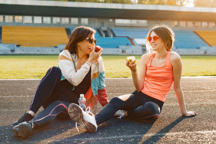 Dwie dziewczyny siedzą na bieżni i jedzą jabłka