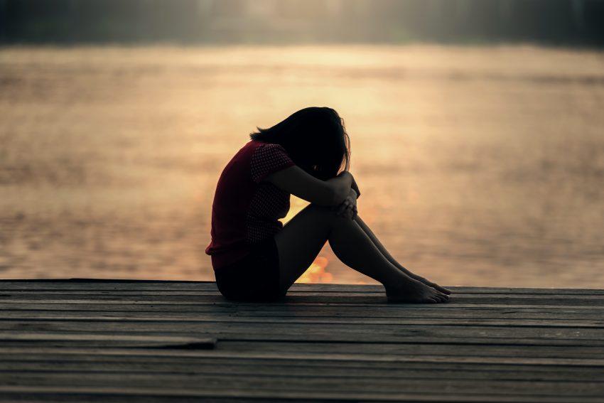 Kobieta siedzi smutna na pomoście